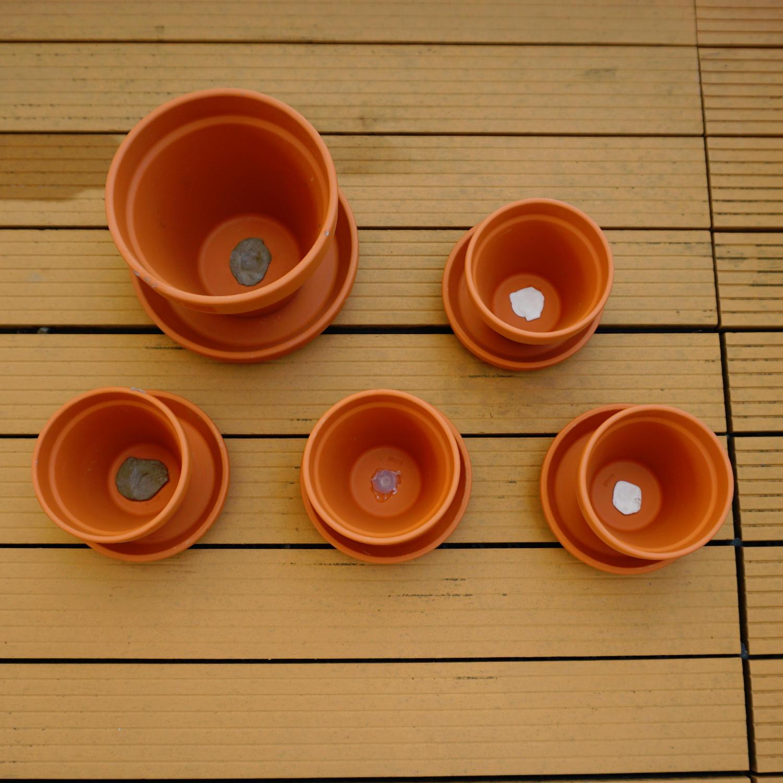Bei verschiedenen Tontöpfen wurden mit unterschiedlichen Klebestoffen die Abflusslöcher verschlossen. Der Tontopf kann so als Wasserspeicher eingesetzt werden.