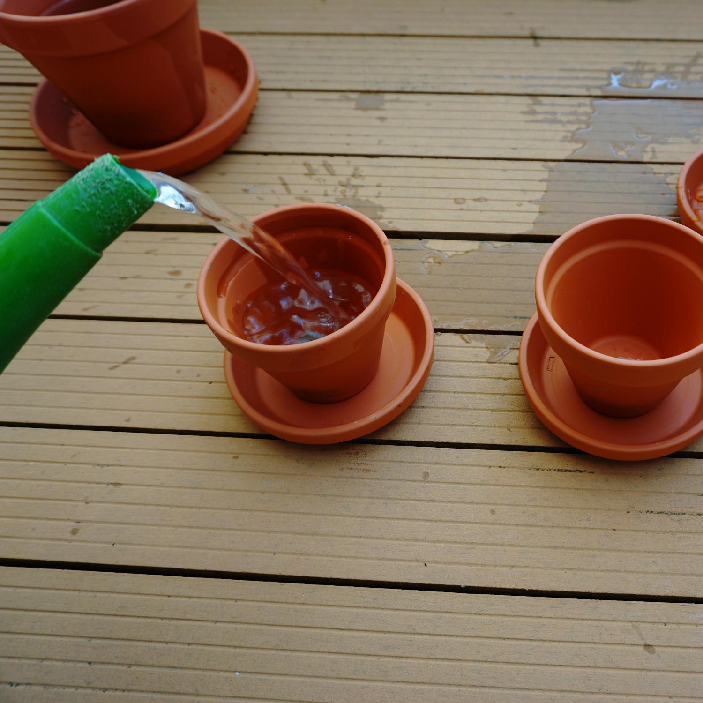 Ein Tontopf mit verschlossenem Loch wird mit Wasser gefüllt und dient als Wasserspeicher.
