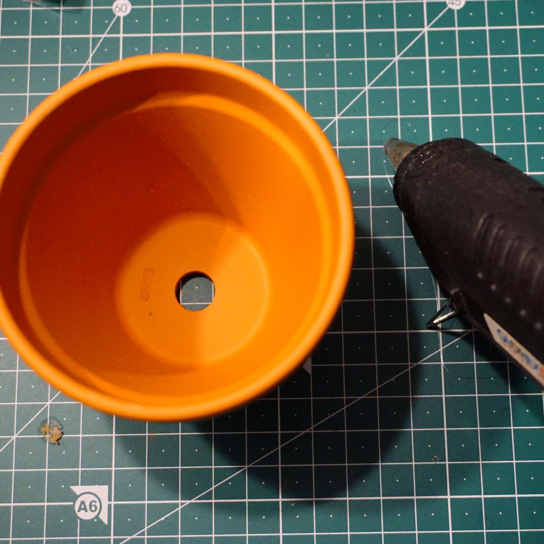 Mit einer Heissleimpistole soll das Abflussloch eines Tontopfs verschlossen werden.